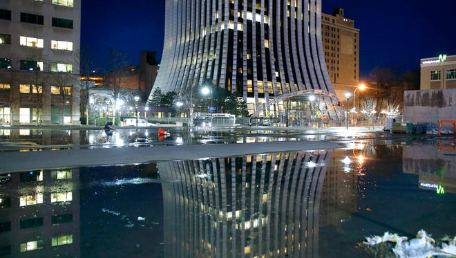 The Metropolitan (former Chase Tower) in downtown Rochester reflected in a puddle.