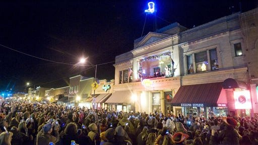 In this Dec. 31, 2013 photo, the crowd cheers as a lighted cowboy boot drops to the roof of the Palace Saloon New Year's Eve on Whiskey Row in downtown Prescott, Ariz. Televised images every year of New York City's glittery ball drop in Times Square have become inextricably linked with New Year's Eve. But Times Square isn't the only place to ring in the new year with an object dropping from the sky at midnight. (AP Photo/The Daily Courier, Les Stukenberg)