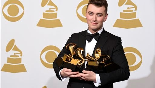"""Sam Smith poses in the press room with the awards for best new artist, best pop vocal album for """"In the Lonely Hour"""", song of the year for """"Stay With Me"""", and record of the year for """"Stay With Me"""" at the 57th annual Grammy Awards at the Staples Center on Sunday, Feb. 8, 2015, in Los Angeles."""