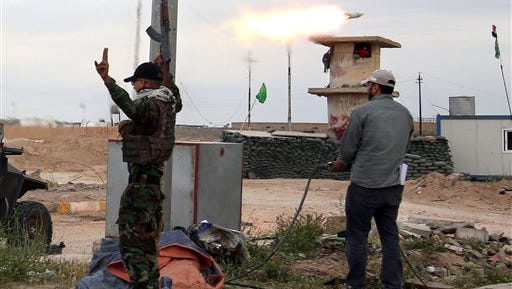 Members of an Iraqi Shiite militant group called Imam Ali Brigades launch rockets against Islamic State group positions during clashes in Tikrit, 130 kilometers (80 miles) north of Baghdad, Iraq, Tuesday, March 24, 2015. (AP Photo/Khalid Mohammed)