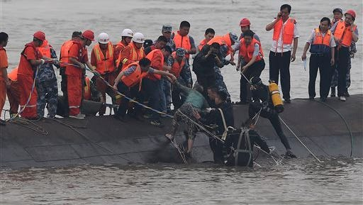 In this photo released by China's Xinhua News Agency, rescuers save a survivor, center, from the overturned passenger ship in the Jianli section of the Yangtze River in central China's Hubei Province Tuesday, June 2, 2015. Rescuers pulled several survivors to safety after hearing cries for help Tuesday from inside a capsized cruise ship that went down overnight in a storm on China's Yangtze River, state broadcaster CCTV said. (Cheng Min/Xinhua via AP) NO SALES
