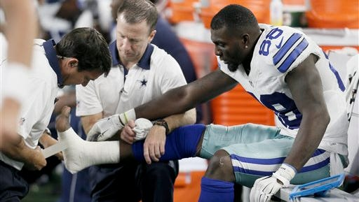 Dallas Cowboys wide receiver Dez Bryant (88) is tended to on the sideline after injuring his foot during Sunday's game.
