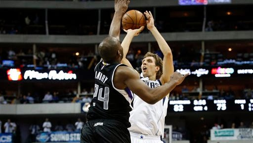 Dallas Mavericks forward Dirk Nowitzki (41) shoots over Sacramento Kings' Carl Landry (24) in the second half of an NBA basketball game.