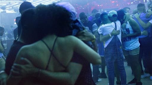 FILE - In this June 19, 2016, file photo, Club goers embrace at the approximate time one week ago that the Pulse nightclub mass shooting began as the music is turned off on the dance floor to observe a moment of silence at Parliament House, an LGBT nightclub early in Orlando, Fla.