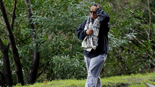 The mother of a missing 18-year-old woman places her hand to her head after viewing the scene where her daughter's car careened off the road Monday on Niles Canyon Road near Fremont. The unidentified woman's car plunged into rushing waters after colliding with another vehicle on Saturday and is suspected as being in the submerged vehicle. (AP Photo/Ben Margot)