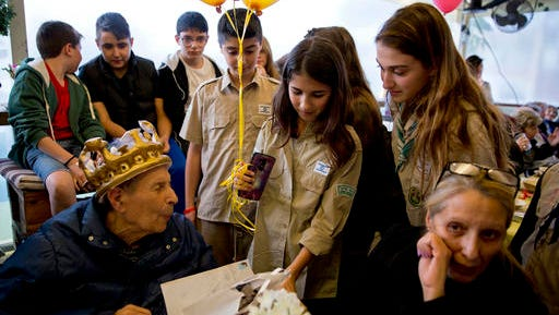 In this Wednesday, Jan. 24, 2017 photo, Israeli Holocaust survivor, Ernest Weiner, wearing crown, is visited by scouts during his birthday in a restaurant in the central Israeli city of Ramat Hasharon. More than 100 fellow Holocaust survivors and advocates on their behalf gathered for the 92nd birthday party of Ernest Weiner -- a blind and widowed survivor who uses a wheelchair to get around and still lives on his own. As home to the world's largest survivor community, Israel is grappling to serve the needs of the thousands of people like Weiner who are living out their final days alone.