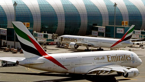 FILE - This May 8, 2014 file photo shows Emirates passenger planes at Dubai airport in United Arab Emirates. The U.S. government is temporarily barring passengers on certain flights originating in eight other countries from bringing most types of electronics in their carry-on luggage. A U.S. official tells The Associated Press that the ban beginning Tuesday, March 21, 2017, affects airports in 10 cities of Cairo in Egypt; Amman in Jordan; Kuwait City in Kuwait; Casablanca in Morocco; Doha in Qatar; Riyadh and Jeddah in Saudi Arabia; Istanbul in Turkey; and Abu Dhabi and Dubai in the United Arab Emirates. in the Middle East, North Africa and Turkey.