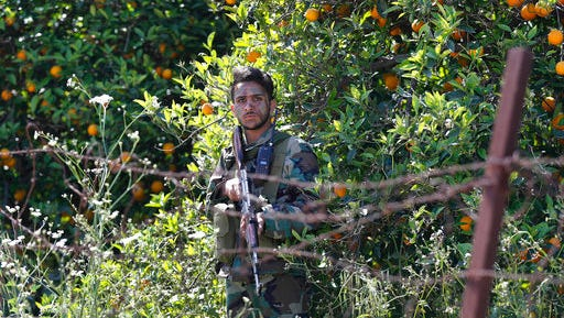 A Hezbollah fighter takes his position between orange trees, at the coastal border town of Naqoura, south Lebanon, Thursday, April 20, 2017. The border tour is the first since an inconclusive month long war between Israel and Hezbollah in 2006, and comes amid heightened tensions along the border between the old adversaries, with each side promising to inflict massive casualties on the other in any upcoming war.