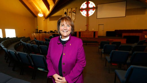 In this Wednesday, April 19, 2017, photo, Bishop Karen Oliveto poses for a photo in the sanctuary of a United Methodist Church in Highlands Ranch, Colo. The top court in the United Methodist Church on Tuesday, April 25, will consider whether the election of Oliveto, the first openly lesbian Methodist bishop, violated church law barring clergy who are ``self-avowed practicing homosexuals.''