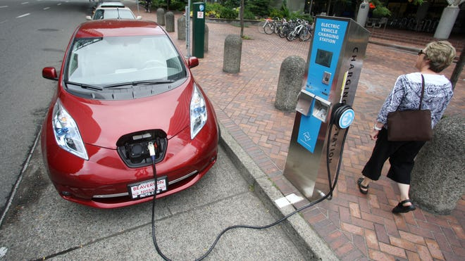 A Nissan Leaf charges at an electric vehicle charging station  in Portland, Ore.