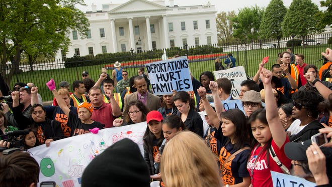 Demonstrators stand outside the White House in Washington, Monday, April 28, 2014, to demand President Barack Obama to stop deportation of immigrants. People were arrested outside the White House in an act of disobedience for family unity and to end the deportations occurring under the Obama's Administration.