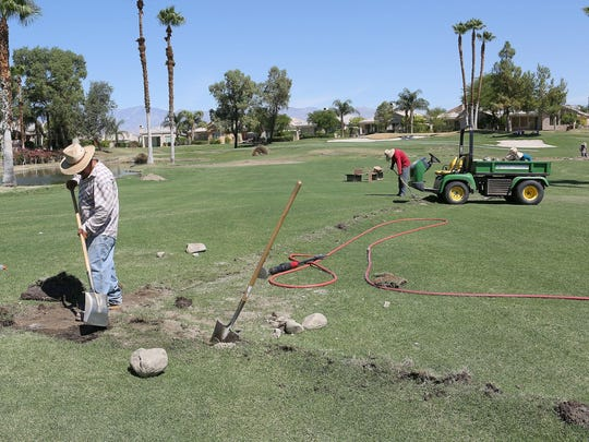 Workers install piping for a new, water-efficient irrigation system at Desert Princess Country Club in Cathedral City on Aug. 4, 2015.