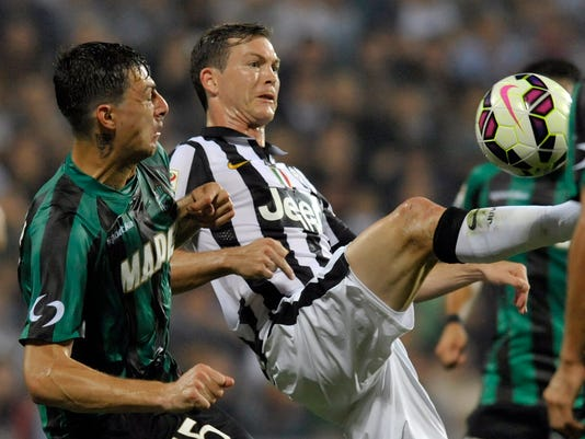 Sassuolo's Francesco Acerbi, left, competes for the ball with Juventus's Stephan Lichtsteiner, during their Serie A soccer match at Reggio Emilia's Mapei stadium, Italy, Saturday, Oct. 18, 2014. (AP Photo/Marco Vasini)