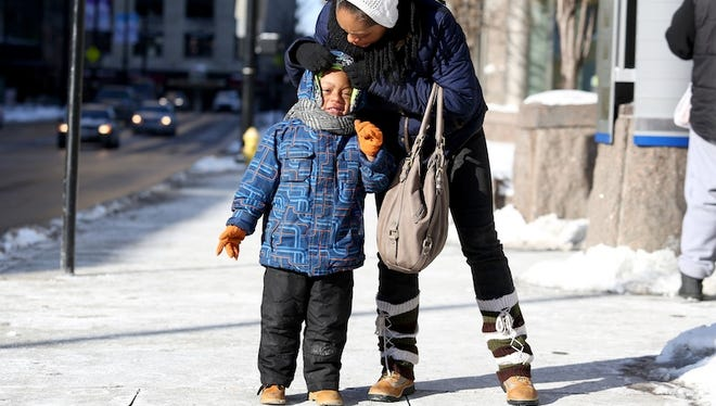 Candice Black of South Fairmount adjusts the hat of her 4-year-old son, Lorenzo before catching their bus at Government Square in downtown Cincinnati. Record-low temperatures and dangerous wind chills hit the area Thursday morning, with wind chill readings between -20 and -30 degrees.
