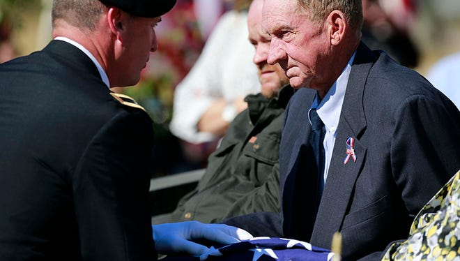 In this photo taken Oct. 20, 2015, Gen. John Rhodes, left, presents the American flag that draped the casket with some remains of Army Cpl. George H. Mason, who fought in the Korean War and was buried near his parents in his north Mississippi hometown of Byhalia, Miss.,  to his brother Albert Mason. Mason, who was 19 at the time, had been missing in action since Feb. 14, 1951 near Chuam-ni, South Korea.
