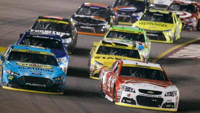 Kevin Harvick (4) leads Joey Logano (22) and the rest of the field into Turn 1 during the NASCAR Sprint Cup Series auto race at Phoenix International Raceway, Sunday, Nov. 15, 2015, in Avondale, Ariz.