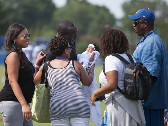 Robert Mathis, #98, surrounded by family and friends holds his new daughter after the fourth day of Training Camp Sunday, July 27, 2014, at Anderson University.