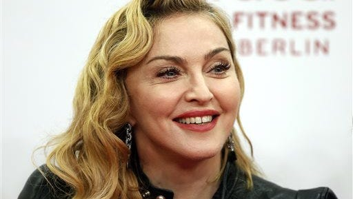 """In this file photo, U.S. pop star Madonna smiles during her visit at the """"Hard Candy Fitness"""" center in Berlin. Madonna is defending herself against criticism after she posted Instagram photos of Martin Luther King Jr. and Nelson Mandela that were altered to look like her own image on her new album."""
