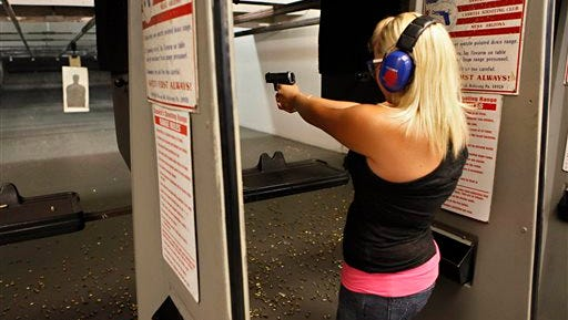 FILE - In this April 6, 2010 file photo, Sarah Bard, of Gilbert, shoots at Caswell Shooting Club in Mesa, Ariz. The Arizona Senate is set to debate legislation Monday, March 30, 2015 that would allow residents with concealed carry permits to bring their guns into government buildings. (AP Photo/Matt York, File )