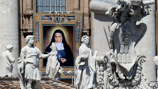 A tapestry showing St. Marie Alphonsine Ghattas hangs from a balcony of St. Peter's Basilica at the Vatican, on Sunday, May 17, 2015. Pope Francis canonized two nuns from what was 19th Century Palestine on Sunday in hopes of encouraging Christians across the Middle East who are facing a wave of persecution from Islamic extremists. Sisters Mariam Bawardy and Marie Alphonsine Ghattas were among four sisters who were made saints Sunday at a Mass in a sun-soaked St. Peter's Square.