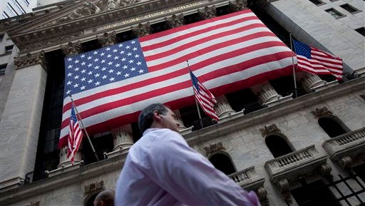 In this Monday, Aug. 8, 2011 file photo, a pedestrian walks past the New York Stock Exchange in New York. Optimism over the prospects of a deal to avoid a Greek debt default and the country's potential exit from the euro shored up global stock markets once again on Tuesday.