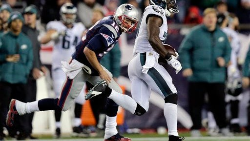 Eagles safety Malcolm Jenkins runs past New England Patriots quarterback Tom Brady (12) on his 99-yard interception return for a touchdown in the third quarter Sunday.