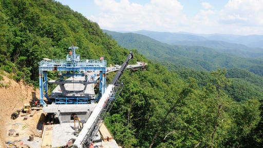 FILE - In this June 13, 2012, file photo, workers use a specialized crane to place a concrete segment onto an 800-foot bridge in an area of the unfinished Foothills Parkway near Walland, Tenn. Work is underway to complete the extension of the scenic route near the northern boundary of the Great Smoky Mountains National Park,. (Curt Habraken/The Mountain Press via AP, File).