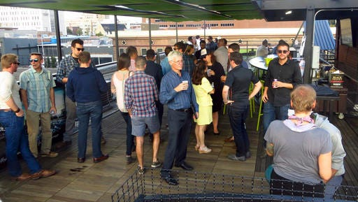 In this Sept. 22, 2016 photo, business owners in the new marijuana industry mingle at a political fundraiser in Denver. Business owners are replacing idealists in the pot-legalization movement as the nascent marijuana industry creates a donor base of entrepreneurs willing to spend to change drug policy. (AP Photo/Kristen Wyatt)