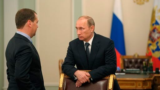 In this photo taken on Thursday, July 17, 2014, Russian President Vladimir Putin, right, speaks to Prime Minister Dmitry Medvedev after a moment of silence mourning the victims killed in the Malaysia Airlines plane crash on Thursday, July 17, in Donetsk region of Ukraine prior a meeting at the Novo-Ogaryovo residence outside Moscow. (AP Photo/RIA-Novosti, Alexei Druzhinin, Presidential Press Service)