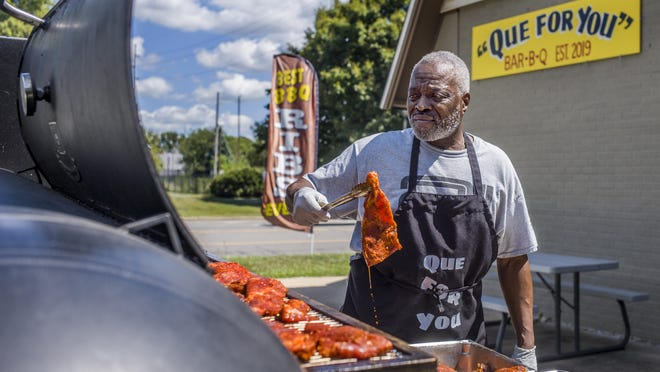 Dan Ruffin loads the smoker with ribs destined to become rib tips at Que For You, the barbecue restaurant he owns with his brother, John, at 301 N. MacArthur Hwy. in Peoria Wednesday, August 19, 2020. Dan Ruffin recently retired as social studies teacher and head basketball coach at Peoria High School.