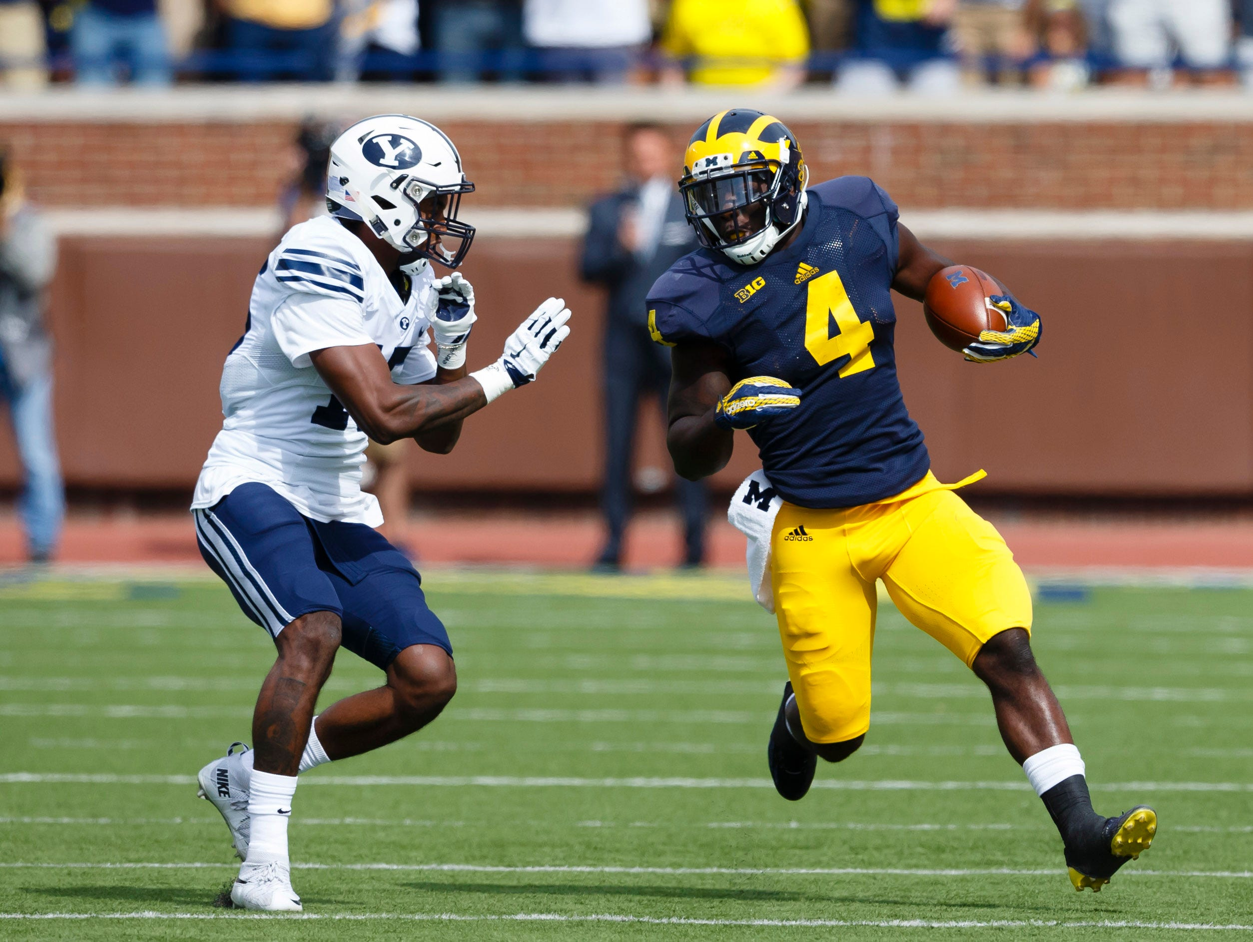 Sep 26, 2015; Ann Arbor, MI, USA; Michigan Wolverines running back De'Veon Smith (4) rushes on Brigham Young Cougars defensive back Michael Davis (15) in the first quarter at Michigan Stadium.