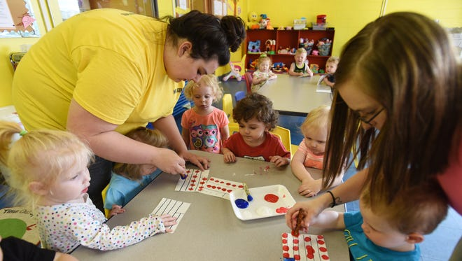 Kirsten Evans, left, and Megan Carpenter work with toddlers at Little Barnyard Childcare Center in Zanesville.