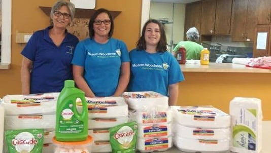 Claudia Fetter (left) accepts the paper products donations from Modern Woodmen. She representsSaint Paul's Lutheran Church in Waldo, which is one of the eightlocal churches who help provide a neighborhood supper. From left, areClaudia Fetter, Lori Seckel and Emily Seckel.