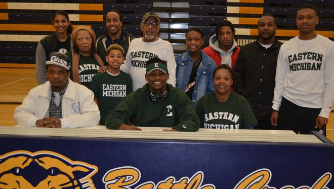 Battle Creek Central football standout Darrell Banks signs to play at Eastern Michigan University. He is joined by his parents, sitting, Darrell Banks and Valena Stanley, along with friends and family.