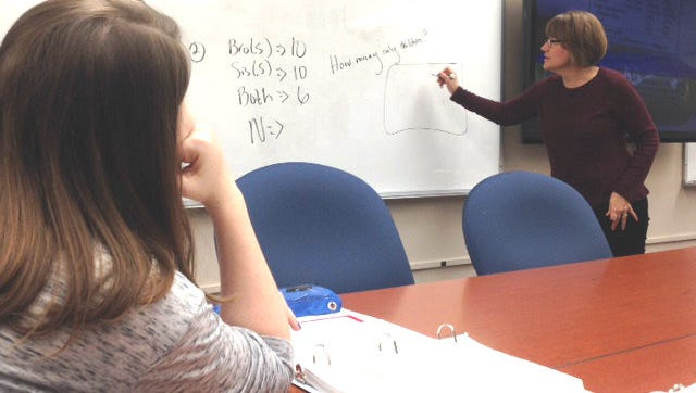 A DMACC student looks on as professor Julie Hartzler explains a concept in a remedial math course at DMACC's Ankeny campus.