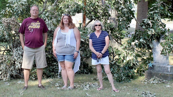 Gary Metz, Brandy Eckert and Elizabeth Campbell, members of the Old Centreville Cemetery committee, near a large limb toppled by wind.