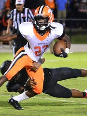 South Gibson's Dre McAllister attempts to avoid being tackled by a Trinity Christian Academy defender Friday evening.