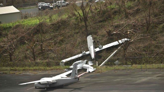 Aircraft damaged in the passing of Hurricane Maria are scattered along the runway at the airport in Vieques on Wednesday, Sept. 27.