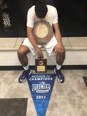 Evansville native Rasheide Bell poses with his MVP plaque and NJCAA Division II Region IV championship banner.