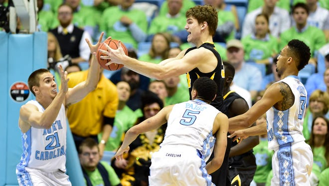 Iowa Hawkeyes center Adam Woodbury (34) with the ball as North Carolina Tar Heels forward Jackson Simmons (21) and guard Marcus Paige (5) and forward J.P. Tokoto (13) defend in the second half. The Iowa Hawkeyes defeated the North Carolina Tar Heels 60-55 at Dean E. Smith Center.