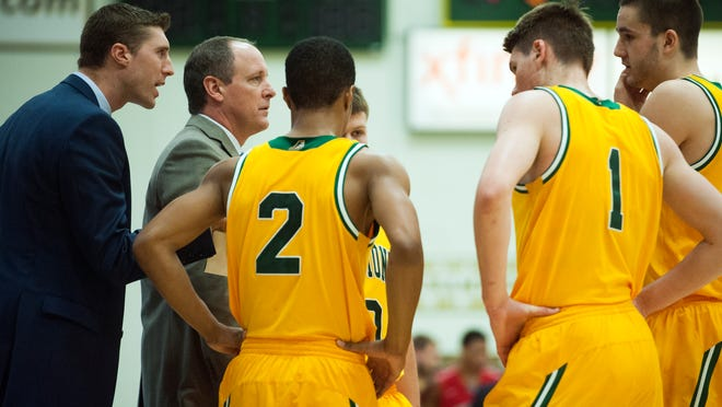 Vermont head coach John Becker talks to his players during a timeout in the men's basketball game between the Stony Brook Seawolves and the Vermont Catamounts at Patrick Gym last week.