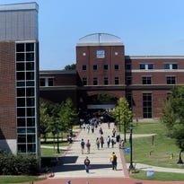 Students and others walk along the sidewalk near the student union at Middle Tennessee State University.