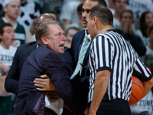 Michigan State coach Tom Izzo is held back by assistant coach Mike Garland, left rear, and director of basketball operations David Thomas, center, as he argues a call with official Bo Boroski, right, during the first half of an NCAA college basketball game against Florida Gulf Coast, Sunday, Nov. 20, 2016, in East Lansing, Mich. (AP Photo/Al Goldis)