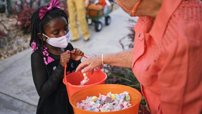 A stock photo of a young girl trick-or-treating for Halloween with a mask on. While there will not be any formal declarations on engaging in Halloween traditions during the COVID-19 pandemic, local health officials are encouraging citizens to practice safe methods or even skipping the holiday this year.
