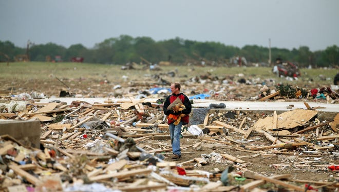 Mark Wade looks through debris after the area was hit by a tornado April 29, 2014, in Vilonia, Arkansas.