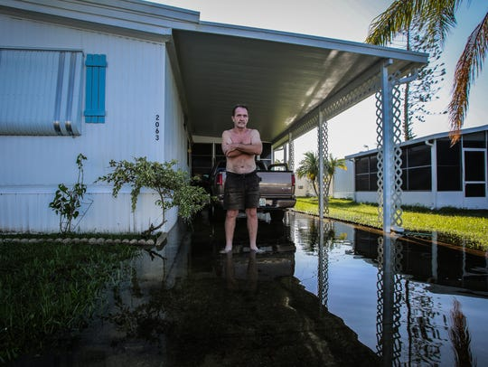 Gary Wright, 66, stands outside his flooded home in