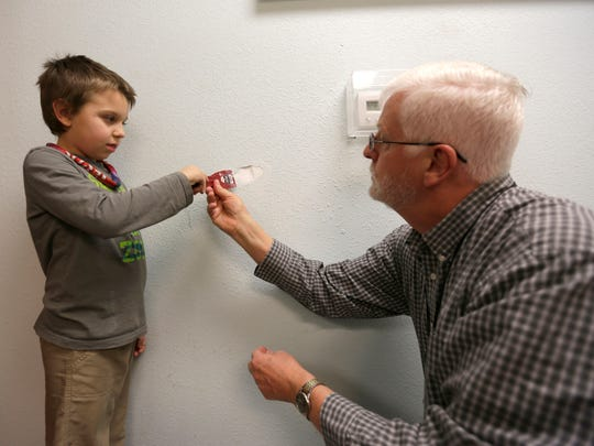Rick Golz, volunteer with Frederic Ozanam Transitional Shelter, helps Tayshan Carter, 7, smooth over a spackling job in the shelter March 23, 2016.