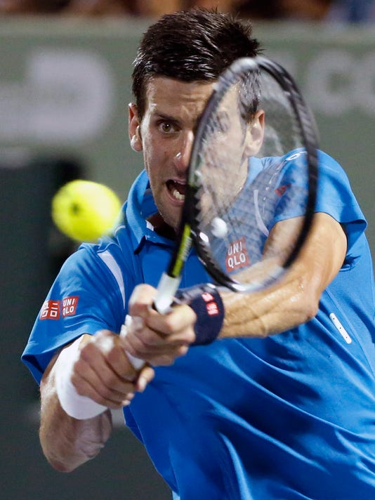 Novak Djokovic of Serbia, returns a shot from Kyle Edmund of Great Britain, during a match at the Miami Open tennis tournament, in Key Biscayne, Fla., Friday, March 25, 2016. Djokovic defeated Edmund 6-3, 6-3. (AP Photo/Wilfredo Lee)