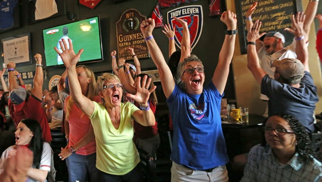 April Hicks, Patty Heffelman and others cheer a US goal in the World Cup finals of USA vs Japan, Sunday, July 5, 2015, as they watch the game at Chatham Tap on Massachusetts Ave.  US won 5-2.