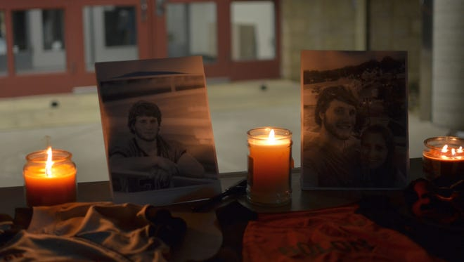 Photos of Tanner Wymer, along with his Solon High School athletics jerseys, are displayed outside the school during a candle light vigil Monday.